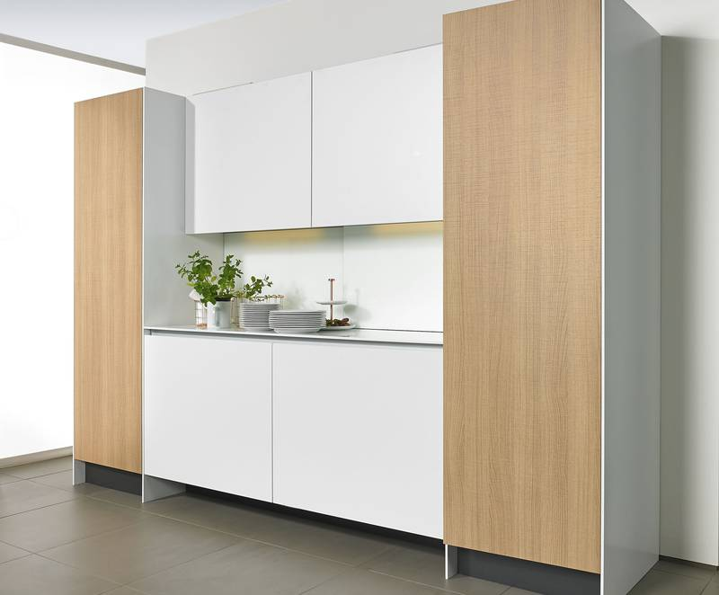 Easys electromechanical opening assistance harmoniously integrates the refrigerator into the design of furniture in a handleless kitchen. Photo: Hettich